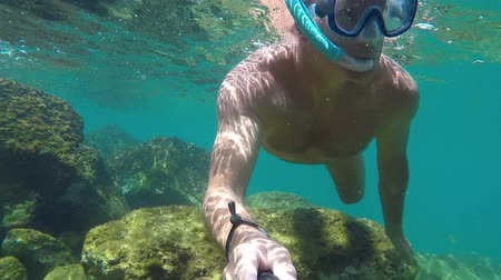 limpid : Young man driving in the Spanish clear ocean water with snorkel and GoPro Hero 5 Black Stock Footage