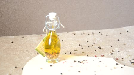 red square : A glass jar with olive oil and spices and sprinkled with pepper on a table