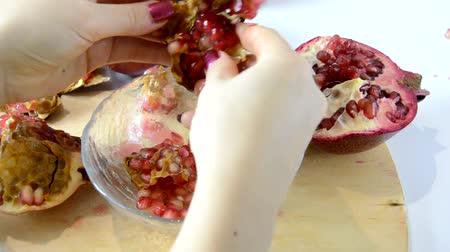 roma : girl cuts a pomegranate and cleans the seeds, puts in a bowl