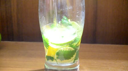 fodormenta : Mojito cocktail alcohol drink top view in highball glass, summer tropical vacation beverage with rum, mint leaves, lime citrus juice, soda water and ice on concrete table.