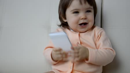 playful infant : Adorable toddler boy sitting on the sofa in the living room and playing with smartphone. Child learning how to use smartphone. Boy texting on the phone. - technology and lifestyle concept