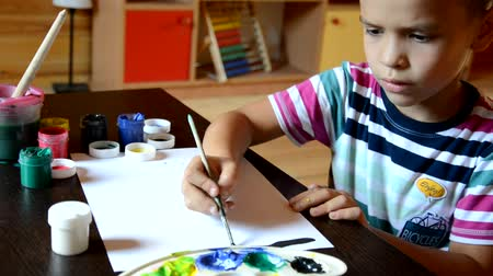 rendes : little cute boy painting at home card on table. boy draws paints and a brush. Thoughtful, serious. Waiting for inspiration. Thinks what to draw. paints on the table. draws a house, the sun, clouds