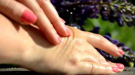 essência : Essential oil bottle in womans hands. A woman does a little on her hands. Moisturizing the skin. Use oil instead of cream. close up of hands