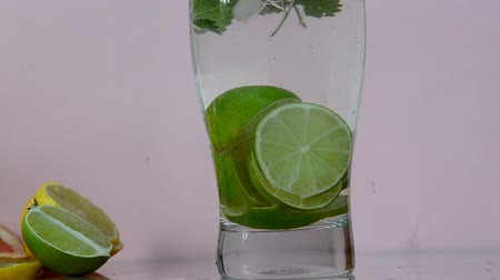 fodormenta : Young girl preparing homemade mojito cocktail, alcoholic or non-alcoholic cocktail, closeup. adds ice to the glass, mint and sliced lime.