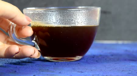 šlehačka : Transparent cup of coffee placed on dark blue surface in front of a window. glass cup with hot black coffee on a dark background with steam