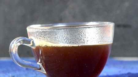 cidra : Transparent cup of coffee placed on dark blue surface in front of a window. glass cup with hot black coffee on a dark background with steam