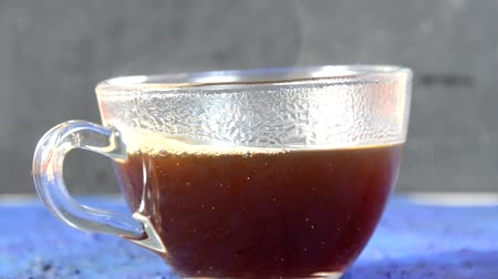 canela : Transparent cup of coffee placed on dark blue surface in front of a window. glass cup with hot black coffee on a dark background with steam