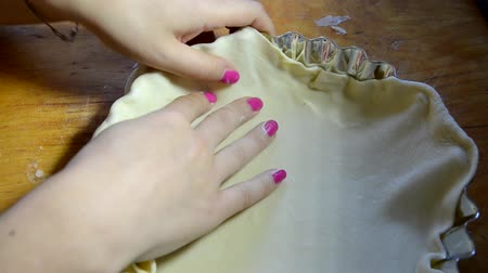 песочное печенье : Hands pressing shaped cookie cutter into dough. The girl is laid out in a baking pan dough