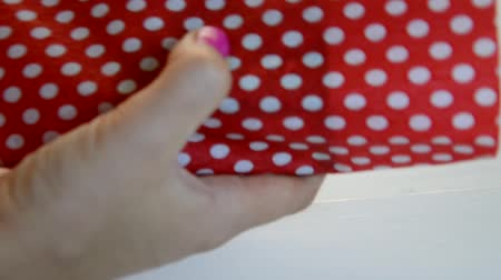 ustalık : Packing presents for holiday, top view. Unrecognizable woman with scissors cut ribbon and red wrapping paper in white peas for wrapping the gift box Stok Video