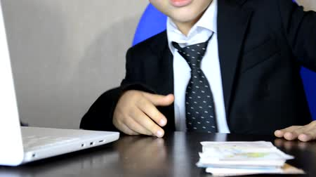 senta : Young businessman using a laptop. Fashion child handsome boy in modern office. sits at a table in an armchair and counts money coins, euro, pounds and dollars.
