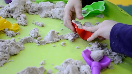 przedszkolak : Creative boy making figures from kinetic sand at lesson