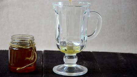dietético : Pour honey into a glass to make a drink. morning glass of water with lemon juice and honey. healthy lifestyle, and health care and proper nutrition for weight loss Stock Footage