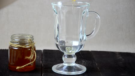 juice jar : Pour honey into a glass to make a drink. morning glass of water with lemon juice and honey. healthy lifestyle, and health care and proper nutrition for weight loss Stock Footage