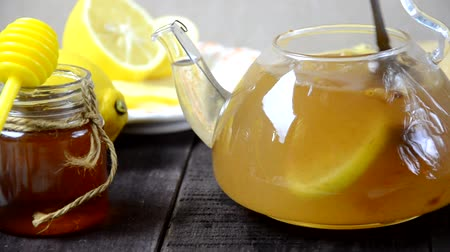 curcuma : put turmeric honey hot water in a teapot to make a healthy drink. Teapot of ginger tea with honey and lemon on wooden table. Cup of ginger tea with honey and lemon on wooden table