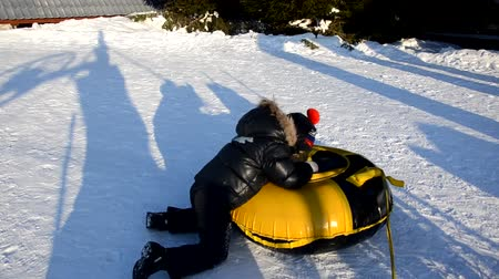 Winter fun, snow, happy children sledding at winter time. Mother, sun and toddler dother Стоковые видеозаписи
