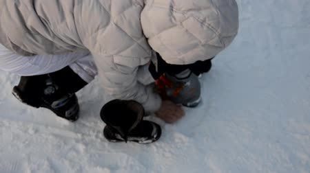 ski boots : getting ready for skiing - fastening the boots. Mom helps her son to wear ski boots. Winter sport. outdoor.