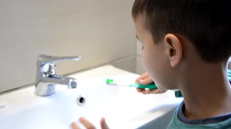 escova de dentes : kid boy brushing teeth and looking at mirror, morning activities, washes his hands Stock Footage