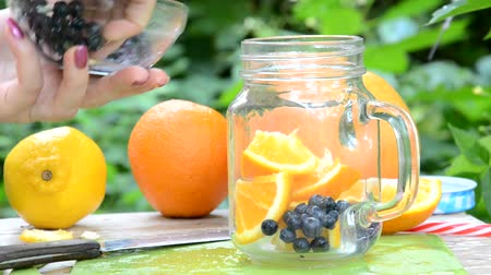 kőműves : woman makes Infused detox water with blueberry, orange and mint. in glass mason jar against a background of green foliage. of health, diet, weight loss, cleansing of toxins, cut fruits by the knife