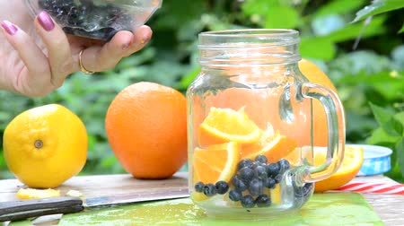 lemoniada : woman makes Infused detox water with blueberry, orange and mint. in glass mason jar against a background of green foliage. of health, diet, weight loss, cleansing of toxins, cut fruits by the knife