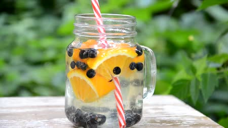 клейкий : woman makes Infused detox water with blueberry, orange and mint. in glass mason jar against a background of green foliage. of health, diet, weight loss, cleansing of toxins, cut fruits by the knife