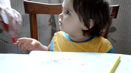 little girl drawing with colored pencils on paper Стоковые видеозаписи