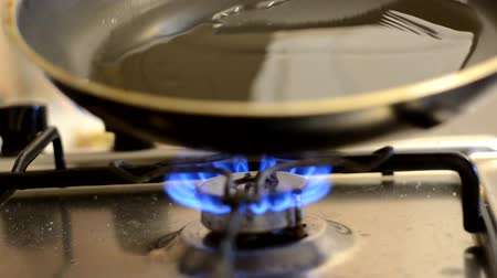 The frying pan is so hot that smoke in the pan. Located on a gas stove.