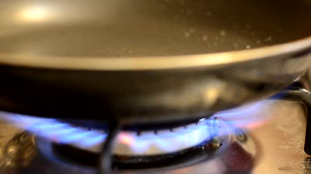 kookgerei : The frying pan is so hot that smoke in the pan. Located on a gas stove.