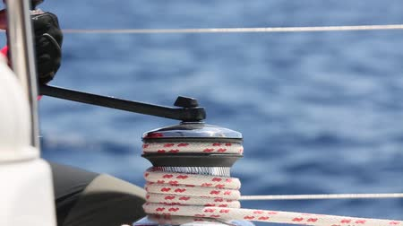 hawser : Sailors hand on a winch of sailing boat. Man pulling ropes, winding sheets around winches. (HD) Stock Footage