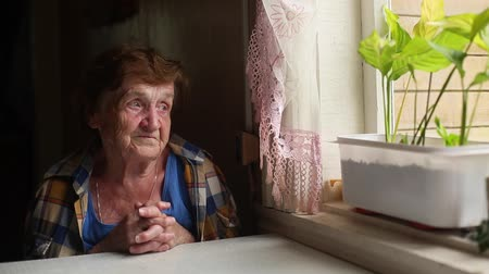 lonely : Old lonely woman sitting near the window in his house. (HD)