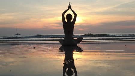 chi : Yoga woman sitting in lotus pose on the beach with reflection in water during sunset.