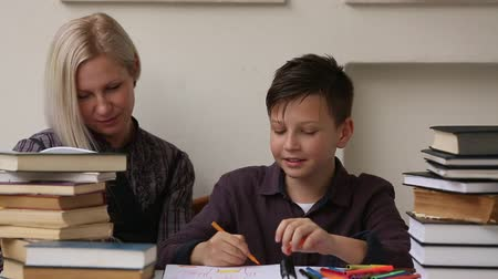 özel öğretmen : Student doing homework with the help of a tutor. HD Stok Video