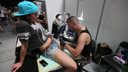 estação de trabalho : KRAKOW POLAND  JUNE 6 2015: People make a tattoos at the 10th International Tattoo Convention in the CongressEXPO Center. This year anniversary TattooFest is tattoo Studio with an area of 2000m2.