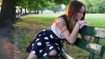 üzgün : Cute teenage girl upset and crying sitting on a Park bench. Problems of teenagers.