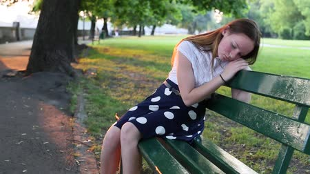 беспокоюсь : Young beautiful girl upset sitting on a Park bench. Problems of teenagers. Стоковые видеозаписи