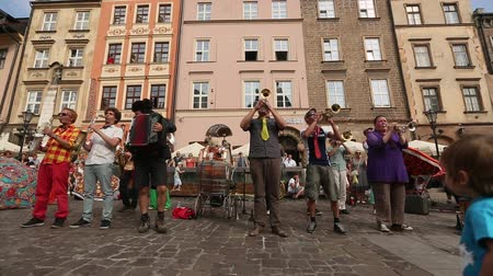lengyelország : KRAKOW, POLAND - JUL 12, 2015: Participants at the annually July 9-12 28th International Festival of Street Theatres - Orchestre International du Vetex BelgiumFrance in the Main Square of Krakow.