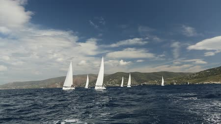 saronic : Boats sailing through waves in the Aegean Sea. Sailboats participate in sailing regatta. Sailing in the wind through the waves. Luxury Yachts. Stock Footage