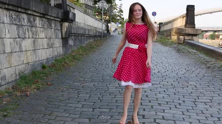 wisla : Young pretty girl in a red dress goes merrily skipping along pavement city waterfront Stock Footage