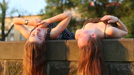 lefekvés : Closeup two young girls girlfriend outdoors lying on the stone curb with long hair hanging down, girl talk to each other. Stock mozgókép