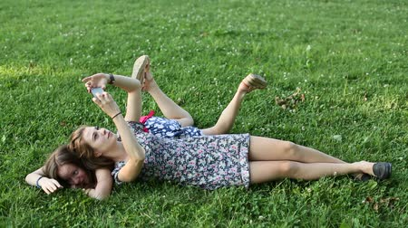 teenager : Cute teen girls girlfriends lying on the lawn taking pictures of himself on a mobile phone, selfie.