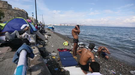escaping : KOS, GREECE - SEP 28, 2015: Unidentified war refugees wash up on the beach. Kos island is located just 4 kilometers from the Turkish coast, and many refugees come from Turkey in an inflatable boats.