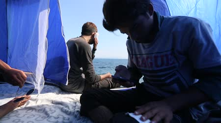 escaping : KOS, GREECE - FEB 28, 2015: Refugees in his tent on the waterfront Aegean sea. Kos island is located just 4 km from the Turkish coast, and many refugees come from Turkey in an inflatable boats.