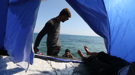 asylum seekers : KOS, GREECE - FEB 28, 2015: Refugees in his tent on the waterfront Aegean sea. Kos island is located just 4 km from the Turkish coast, and many refugees come from Turkey in an inflatable boats.