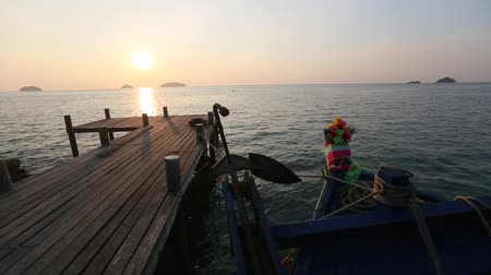 Thai fishing boat and wooden catwalk on the sea coast during sunset.