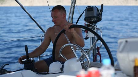 Skipper yachtsman during race, on his sailing yaht boat on the sea.