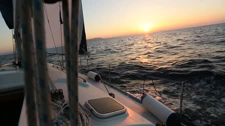 Sailing in the wind through the waves during sunset. Yacht boat shot in full HD at the Aegean Sea. Stock Footage