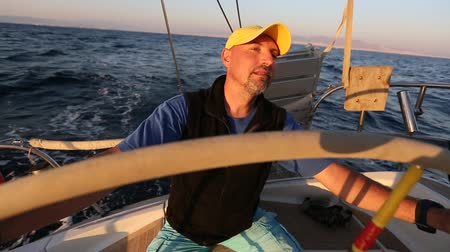 Yachtsman skipper during race, on his sailing yaht boat on the sea. Stock Footage