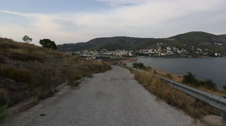 Driving through a motorcycle the serpentine roads of Poros island, Greece.