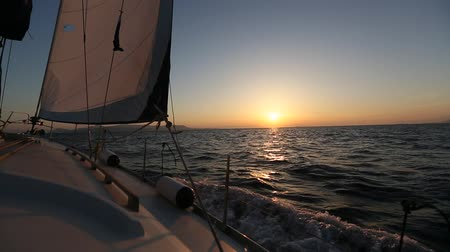 Sailing in the wind through the waves during sunset. Boat shot in full HD in the Aegean Sea. Luxury Yachts.