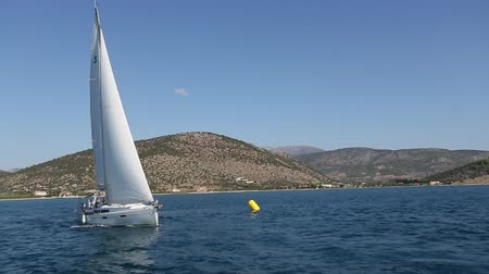 Sailing yacht in the finish during the race regattas near the coastal cliffs in the Aegean sea.