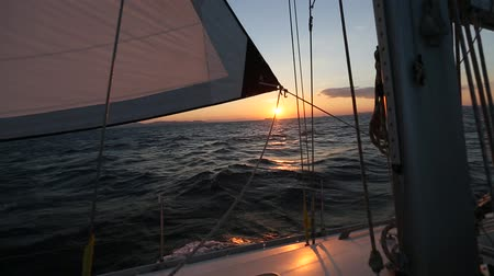 Beautiful sunset at sea shot through the rigging of a sailing yacht boat.